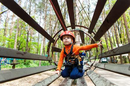 niño escalando: Retrato de 3 años de edad, muchacho llevaba casco y escalada. Niño en un curso abstacle de madera en patio de la aventura