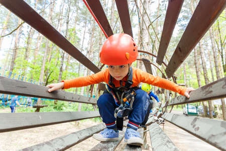 ni�o escalando: Portrait of 3 years old boy wearing helmet and climbing. Child in a wooden abstacle course in adventure playground