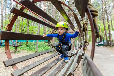 ni�o escalando: Retrato de 3 a�os de edad, muchacho llevaba casco y escalada. Ni�o en un curso abstacle de madera en patio de la aventura