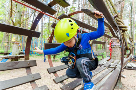 ni�o escalando: Retrato de 3 a�os de edad, muchacho llevaba casco y escalada. Ni�o en una carrera de obst�culos de madera en patio de la aventura