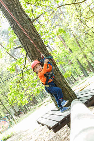 sway: Young boy in helmet walks by pendant tree log at sunny summer day in adventure playground