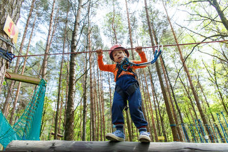 foot bridges: Young boy in helmet walks by pendant tree log at sunny summer day in adventure playground