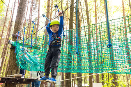foot bridges: Young boy in helmet walks by rope at sunny summer day in adventure playground