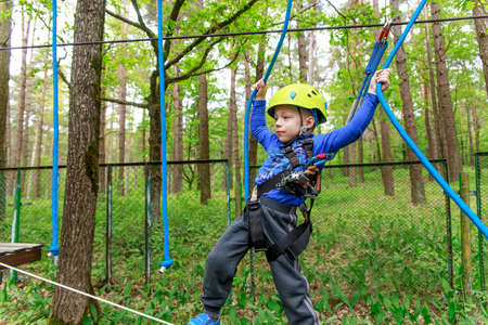sway: Young boy in helmet walks by rope at sunny summer day in adventure playground