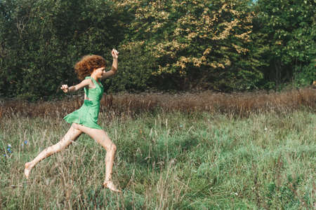 red hand: Young beautiful sexy girl in a green dress runs on a glade Stock Photo