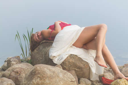 Sexy young woman laying on a stone in fog Stock Photo