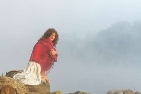 Pretty young woman sits on a stone in fog photo