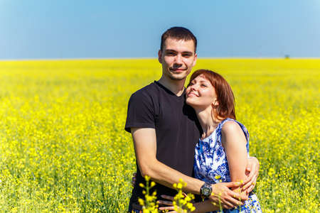 Image of happy couple embracing in yellow meadow at summer