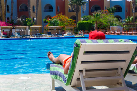 man lying down: Sunbathing by the hotel tourist resort swimming pool, man lying down on a sunlounger looking over the water Stock Photo