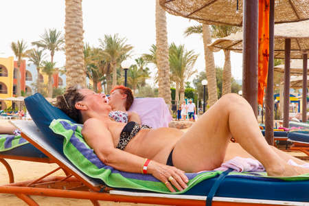 hurghada: HURGHADA, EGYPT - MAY 20: Old women resting on the beach in Arabia Azur resort at May 20, 2015 in Hurghada, Egypt Editorial