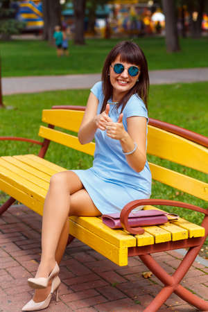 brown haired: A young brown haired woman in blue dress shows thumbs up on a park bench
