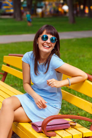 brown haired: A young brown haired woman in blue dress sits on a park bench Stock Photo