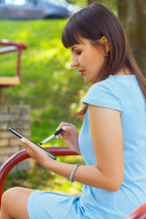 stylus: Young business woman using tablet in park