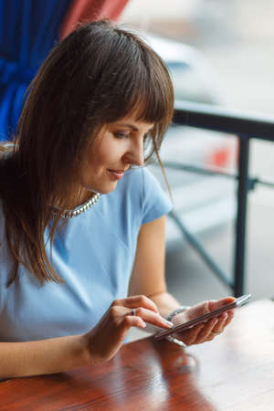 A young woman is using her smart phone at a table outside