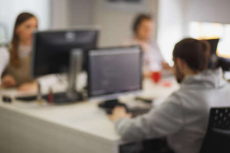 Blurred background picture with software developers during the working process