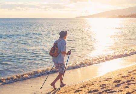 An elderly woman practicing Nordic walking on sunrise