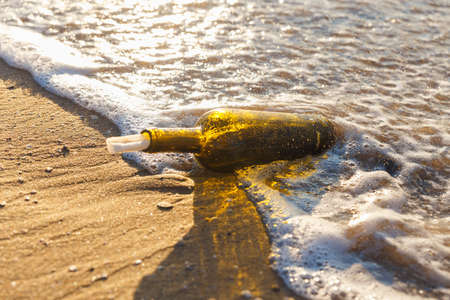 Message in a bottle on a sea shore Stock Photo