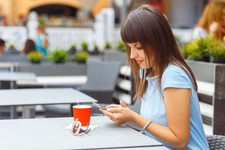 Portrait of beautiful caucasian woman using smartphone in outdoor cafe