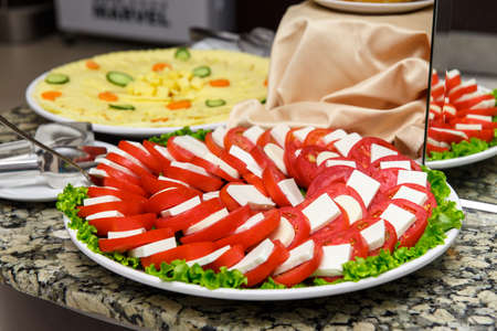 carnes y verduras: A plate of tomatoes and cheeses sliced on the buffet
