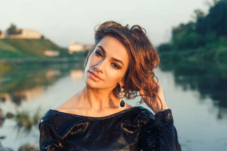 vogue style: Beautiful young fashionable woman posing in dress at the river coast in the evening after sunset. Vogue style. River background.