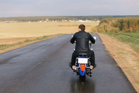 motorsprot: Man on motorcycle going away on an empty road
