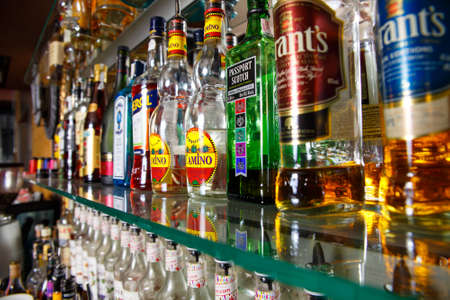 intoxicate: GRODNO, BELARUS - OCT 18, 2016: Blurred alcohol bottles on a bar at the PUB 32 in Grodno, Belarus, October 18, 2016