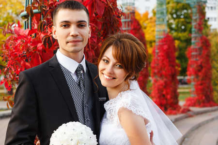 Bride and Groom hugging in autumn park