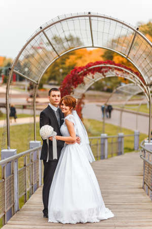 Bride and Groom on walk in autumn park