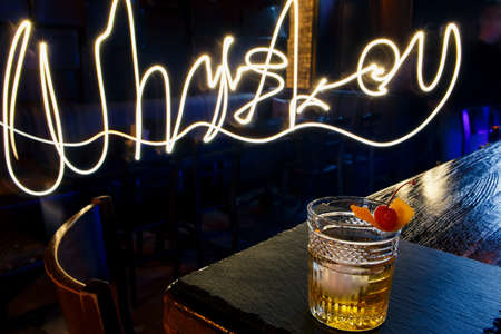 Cocktail RUSTY NAIL and lighting text on black bar background
