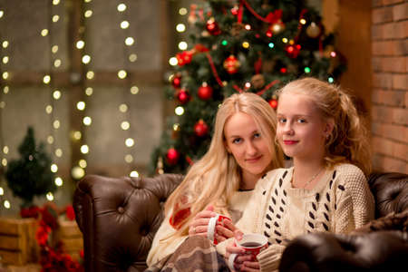 warm clothing: christmas and family concept - mother and daughter talking and drinking tea sitting on sofa at home with Christmas tree