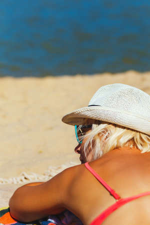 Attractive Young Woman Wearing Bathing Suit Lays On Sand Beach
