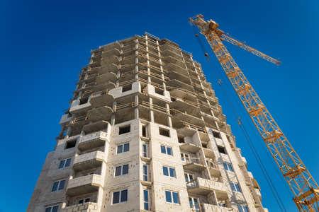 Dos grúas de torre que construyen el cielo azul de trabajo Foto de archivo