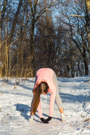 Young girl goes in for sports in winter park. Tilt are one of the general developmental exercises.