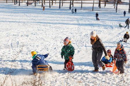 GRODNO, BELARUS - DEC 04: Families enjoy sledding on a snowy hill in a city Park at December 04, 2016 in Grodno, Belarus