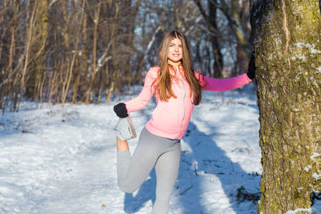 Young girl goes in for sports in winter park. Stretching are one of the general developmental exercises.
