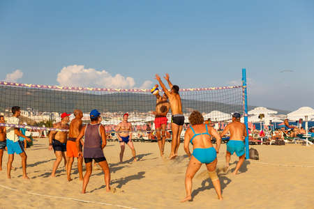 Active adults play the sport of volleyball on the sand beach