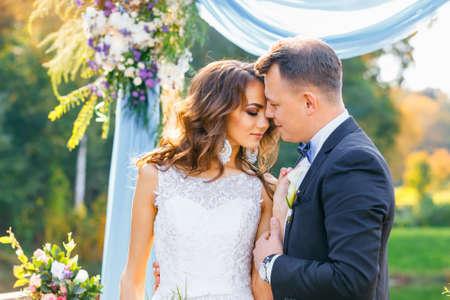 エレガントな巻き毛幸せな新郎新婦屋外の背景湖。創造的なスタイリッシュな結婚式