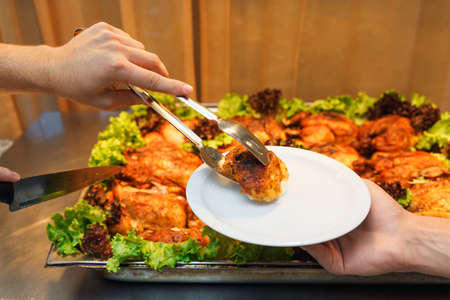 Service in the restaurant. The waiter puts on plate to client a piece of fresh fried chicken. Stock Photo