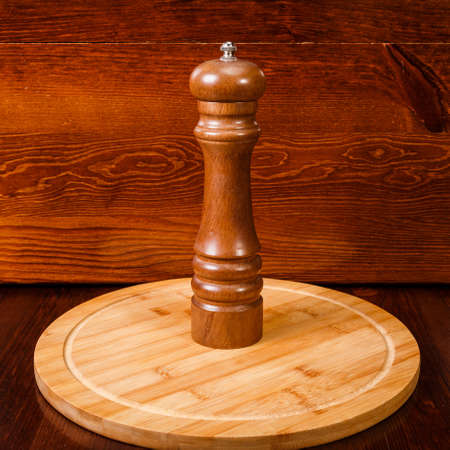 Brown pepper mill standing on wooden background