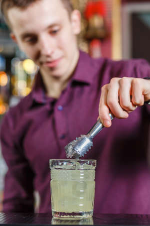 The bartender making cocktail in a nightclub bar
