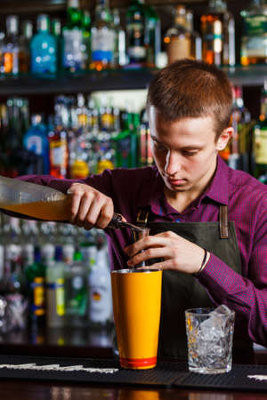 The bartender making cocktail in a nightclub bar. Pouring liquor. Stock Photo