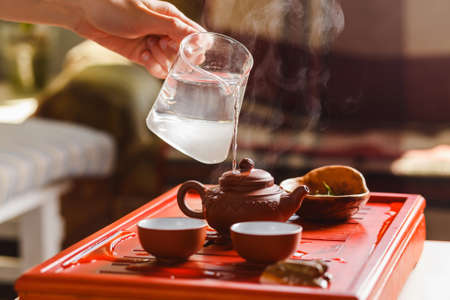 The tea ceremony. The woman rinses the teapot before brewing the tea