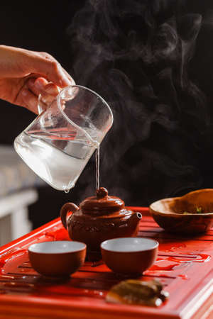 vapore acqueo: The tea ceremony. The woman rinses the teapot before brewing the tea
