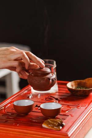 vapore acqueo: La cerimonia del tè. La donna versa il tè in una ciotola di tè. Avvicinamento.