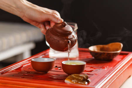 The tea ceremony. Woman pours tea in a tea bowl. Close-up.