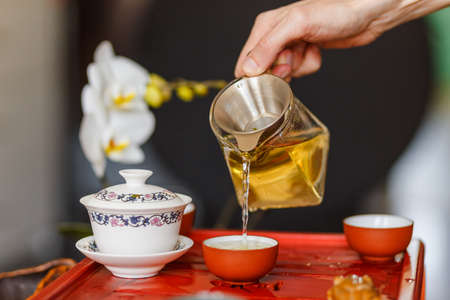 The tea ceremony. The hands of man pouring tea in a tea bowl. Close-up.