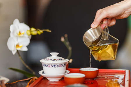 vapore acqueo: The tea ceremony. The hands of man pouring tea in a tea bowl. Close-up.