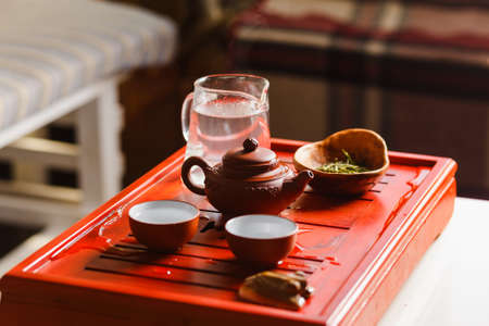 The process of brewing tea at the tea ceremony. Still life with a teapot, two cups and chahe.