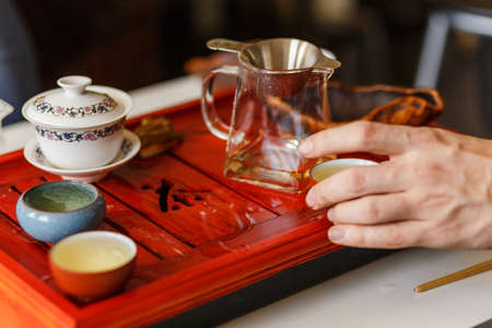 The tea ceremony in process. Men takes the bowl with green tea..