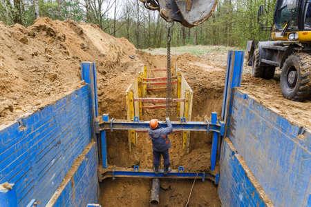 트렌치 벽을 보호하기위한 금속 지지대 설치. 안감은 벽이 쓰러지지 않도록 보호하고 근로자를 구합니다.